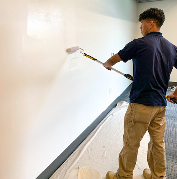 Valley Facility Services Crew member finishes Drywall patch, paint and repair project