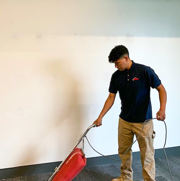 Valley Crew Member Vacuuming preforms Business Cleaning and Sanitizing Services