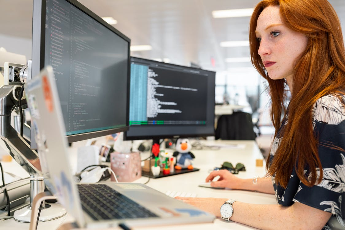 A woman coding on a computer in her new office.